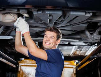 Smiling Mechanic Working Underneath Lifted Car